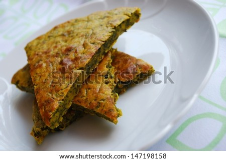 Slices of vegetarian chickpeas cake with herbs in a white dish - stock photo