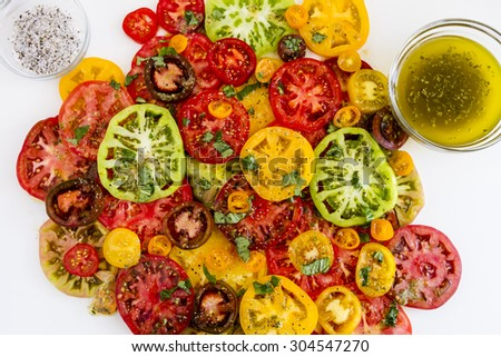 Slices of vine ripe heirloom tomato varieties with fresh basil, salt, pepper, olive oil and fresh herbs on white background - stock photo