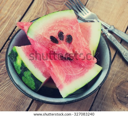 slices of watermelon in a metal bowl on a wooden background toning - stock photo