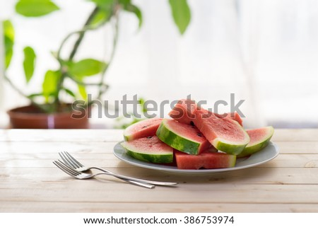 Slices of watermelon on a plate on wooden table with two forks next to window - stock photo