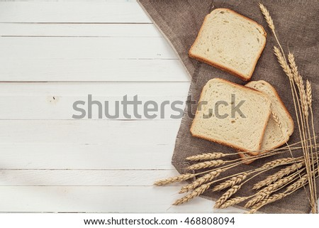 Slices of white bread and wheat ears on sacking on white boards. Space for text.