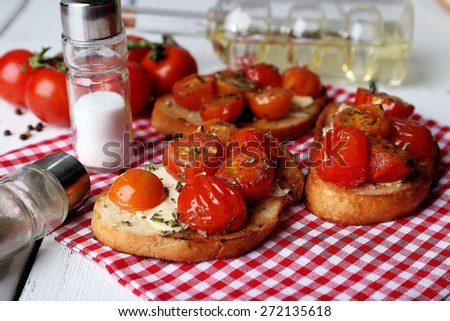 Slices of white toasted bread with butter and canned tomatoes on color wooden planks background - stock photo