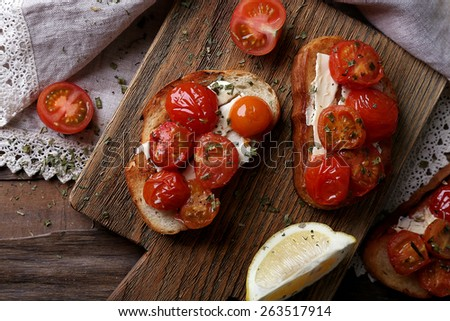 Slices of white toasted bread with canned tomatoes and lime on cutting board on wooden table background - stock photo