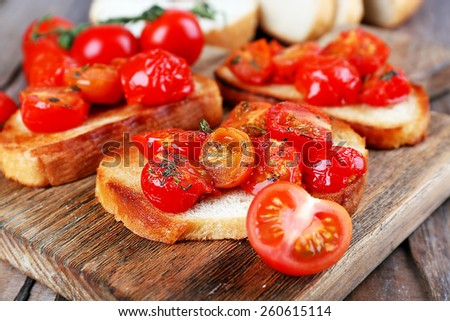Slices of white toasted bread with canned tomatoes on cutting board on wooden table, closeup - stock photo