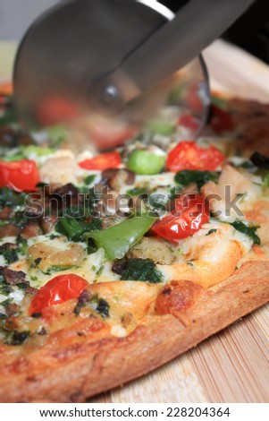 Slicing a thin crust pizza with healthy vegetales with steel pizza cutter and shallow depth of field - stock photo