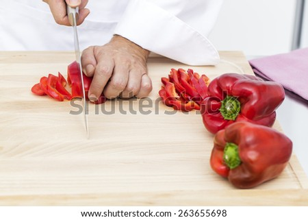 Slicing red peppers on cutting board - stock photo