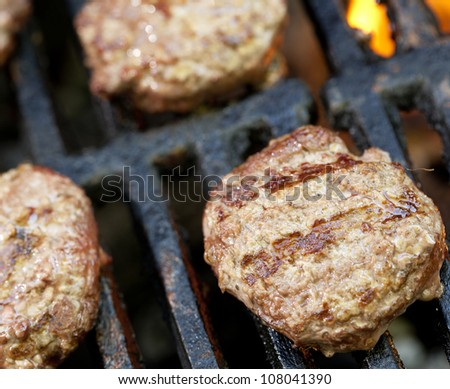Slider hamburgers cooking on a barbecue grill.