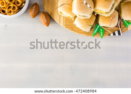 Sliders with veggie tray on the table for the football party.
