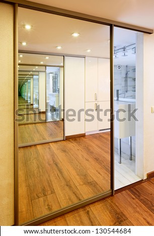 Sliding-door mirror wardrobe in modern hall interior with infinityreflections - stock photo