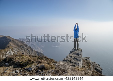 SLIEVE LEAGUE, IRELAND - MARCH 17, 2016: Man practising yoga with arms stretched to the sky in a blue jacket standing at the edge of vertical cliff overlooking vastness of ocean