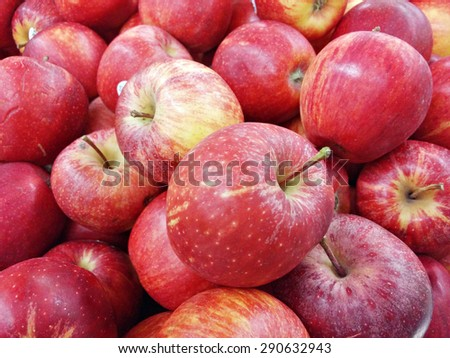 Slightly blur image of red apples on supermarket display rack. Image contains visible noise and blurry due to selective focusing, not suitable for single and for background purpose only.