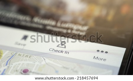 Slightly defocused and closeup of digital screen of smartphone device focusing on Check In and road map - stock photo