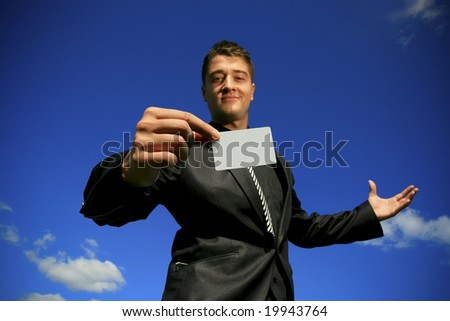 Slightly out of focus face of young man offering a focused card. - stock photo