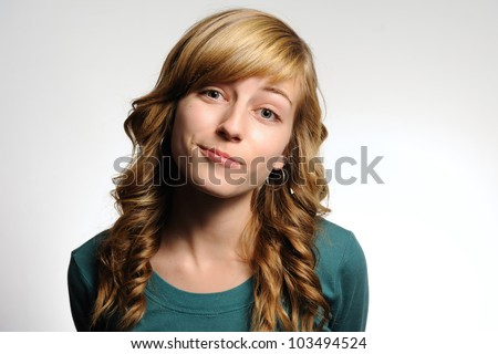 Slightly Smiling Teenage Girl. Teenage girl making a slight smile with a tilted head as if she is bored. Note: not isolated. - stock photo