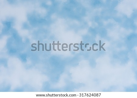 Slightly textured wallpaper with a blue sky and cloud pattern.