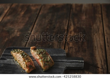 Slightly unfocused two raw pieces of salmon in white wine sauce with spices and herbs presented on stone deck prepared for grill Healthy nutrition meal isolated on side of rustic wooden table - stock photo