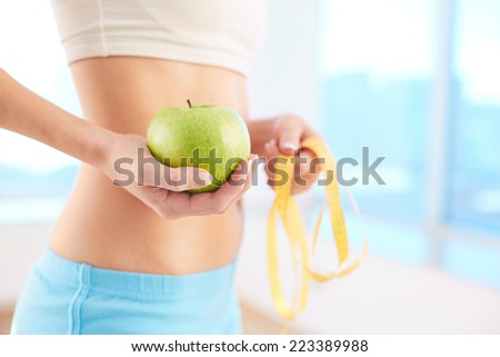 Slim and healthy female holding green apple in hand - stock photo