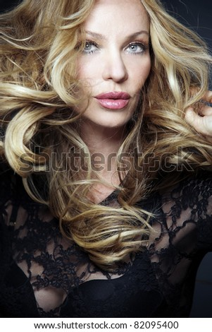 Slim attractive blond woman with long curly hair. - stock photo