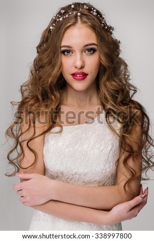 Slim beautiful woman with long hair wearing wedding dress isolated on white - stock photo