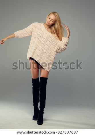 Slim blond female in long black shoes and sweater posing over grey background.
