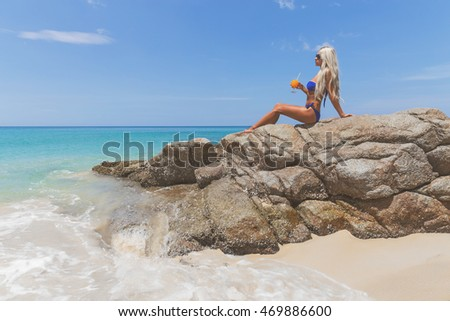 Slim blonde long haired woman in bikini  with orange cocktail on tropical beach