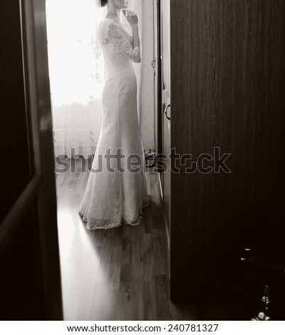 slim bride near the window. elegant wedding dress
