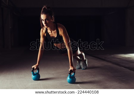 Slim brunette doing push-ups exercises on kettlebells. Cross fit training - stock photo