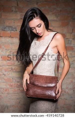 Slim brunette wearing white lace dress posing with handbag - stock photo