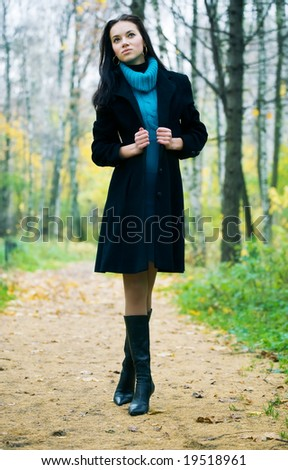 Slim brunette woman walking in a park. Autumn season. - stock photo