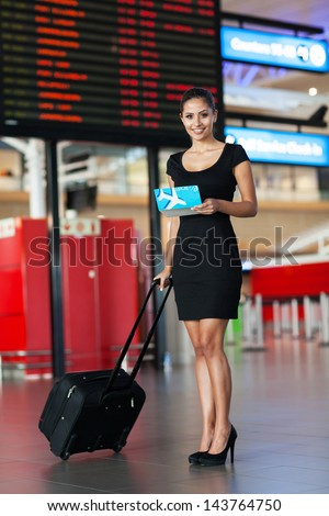 slim businesswoman standing next to flight information board at airport - stock photo