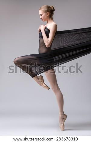 Slim dancer plays with black mesh fabric - stock photo