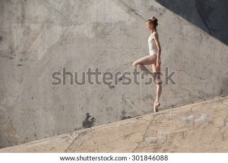Slim dancer stands in a ballet pose and looking down on a gray urban concrete background. Outdoors shooting with sun light. - stock photo