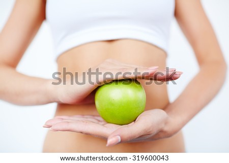 Slim female holding green apple between her palms