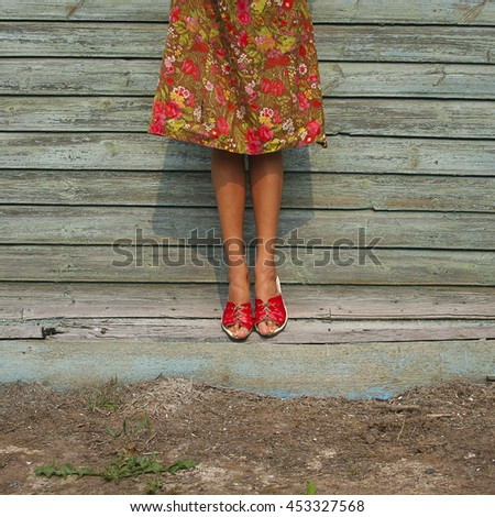 Slim Female Legs and colorful dress on wooden background, country style