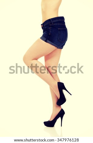 Slim female legs in jeans and high heel shoes.