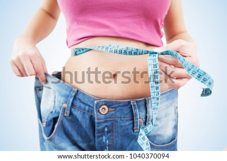 Slim Female measuring her thin waist with a tape measure,  woman in jeans, Unrecognizable person