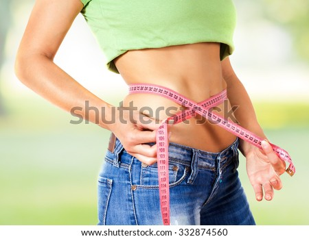 Slim Female with perfect healthy fitness body, measuring her thin waist with a tape measure . Caucasian young woman in jeans. Unrecognizable person.Diet and weight loss concept. - stock photo
