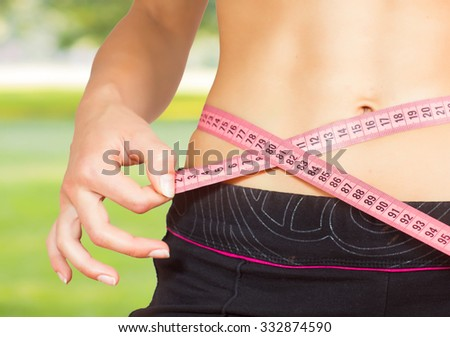 Slim Female with perfect healthy fitness body, measuring her thin waist with a tape measure. Caucasian young woman in sportswear. Unrecognizable person.Diet and weight loss concept.