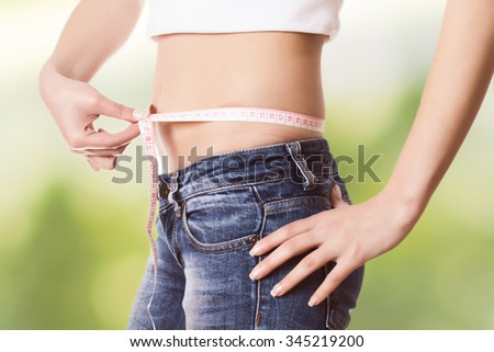 Slim Female with perfect healthy fitness body, measuring her thin waist with a tape measure. Unrecognizable person.Diet and weight loss concept. - stock photo