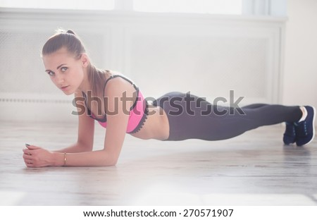 Slim fitnes young girl with ponytail doing planking exercise indoors in a sunlight