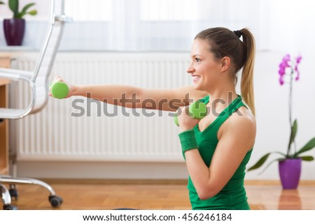 Slim fitness young girl with ponytail doing planking exercise indoors in a sunlight - stock photo