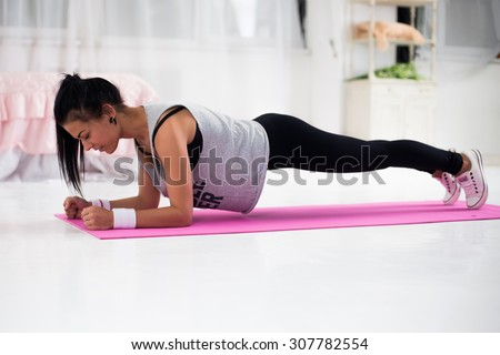 Slim fitness young woman Athlete girl doing plank exercise at home concept training workout crossfit gymnastics cross fit. - stock photo