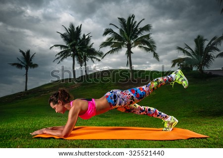 Slim fitness young woman Athlete girl doing plank exercise outside. Concept training workout crossfit gymnastics cross fit. - stock photo
