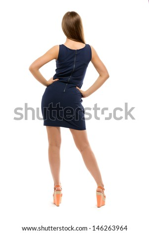 Slim girl in a dress stands back. Isolated on white background - stock photo
