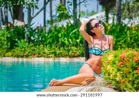 Slim girl in a swimsuit having pleasure and relaxing among tropical greenery