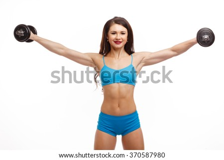 Slim girl is engaged in fitness with dumbbells on white background. Woman holding dumbbells in one hand, fresh and energetic. - stock photo