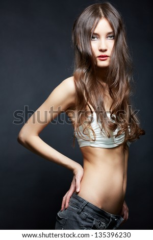 Slim girl looking at camera over black background