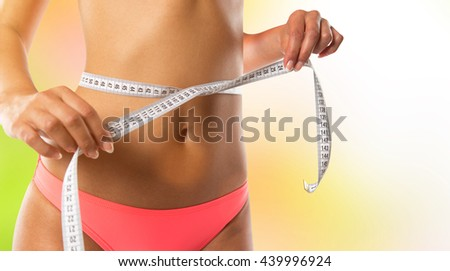 Slim girl measuring her waist, close-up.