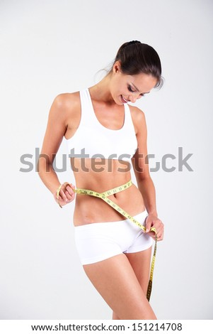 Slim girl with centimeter on gray background - stock photo