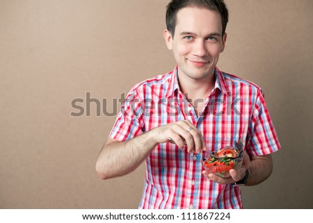 Slim handsome boy eating salad over wooden background. studio shot - stock photo